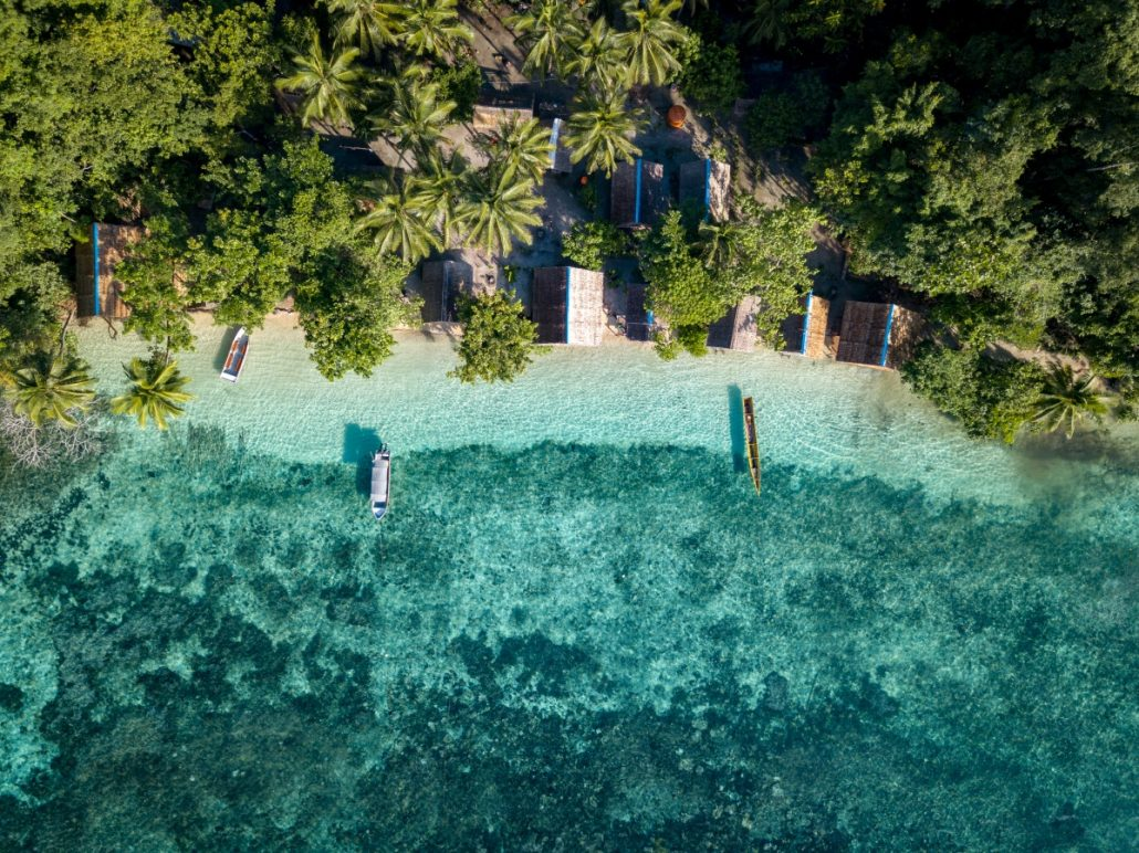 Aerial view of small huts at tropical water.