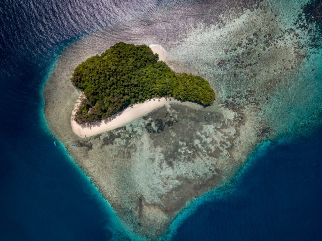 Aerial view of a heart-shaped, tropical island.