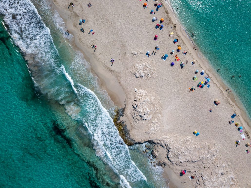 Aerial shot of a narrow beach with sunshades.