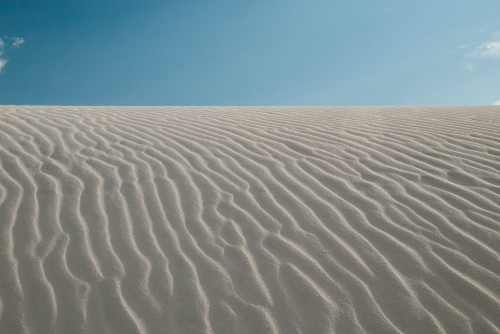 Landscape photograph of the waves on the surface of a white sand dune.