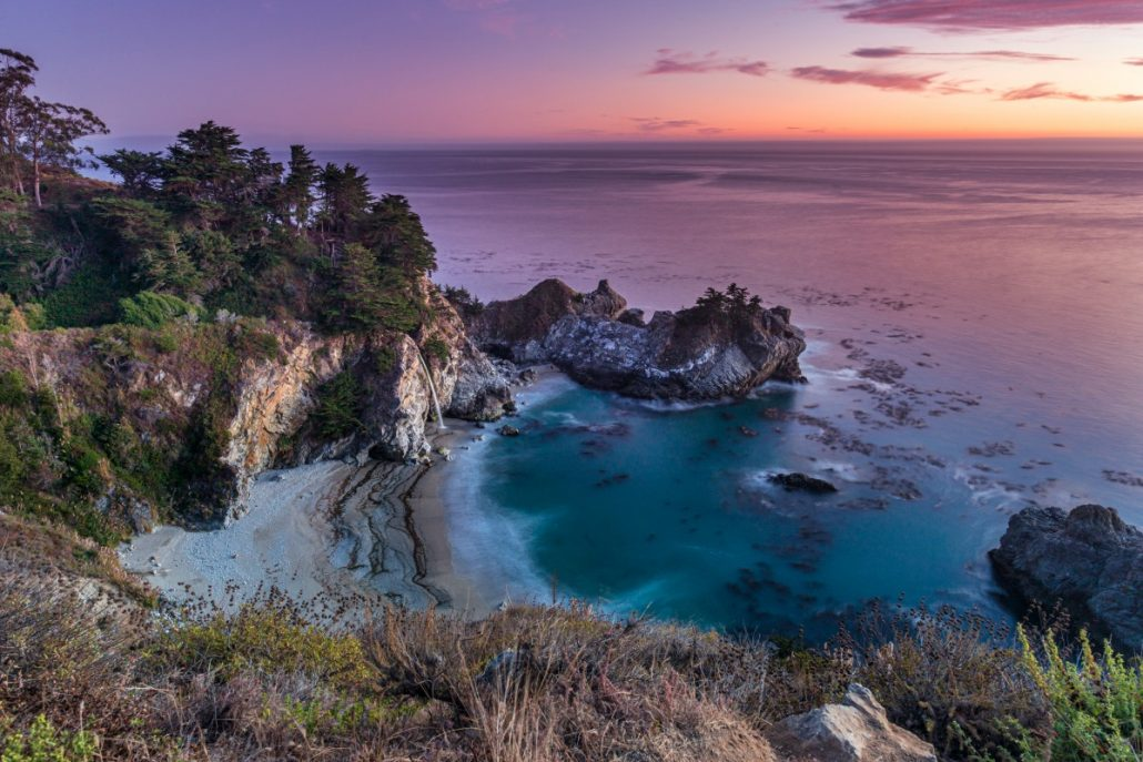 Landscape shot of a beach in a bay with waterfall at sunset.