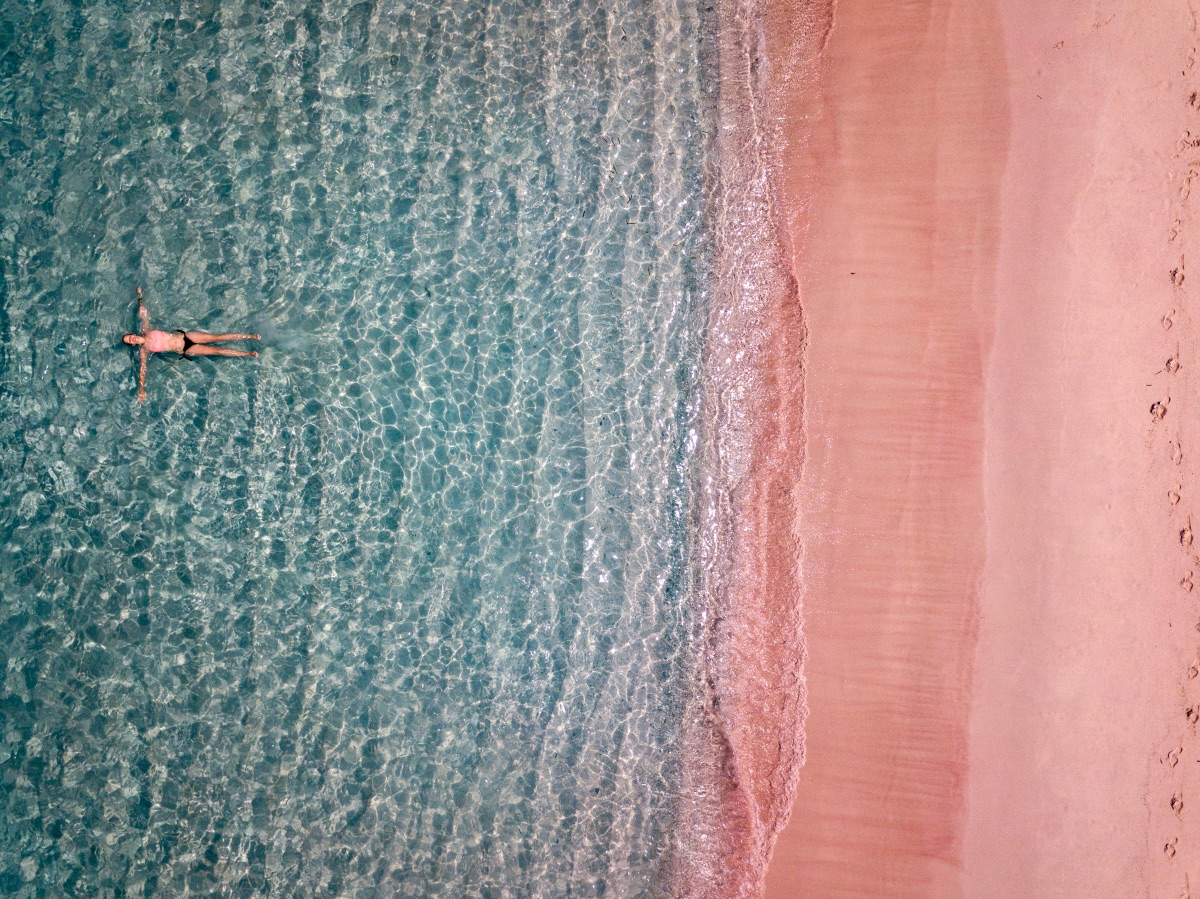 Aerial view of a woman swimming in the sea in front of a pink beach.