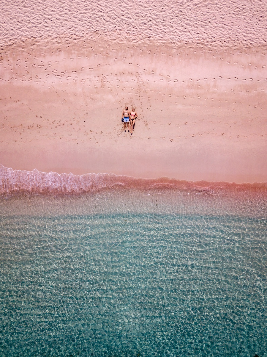 Aerial view of a couple on the beach with pink sand.