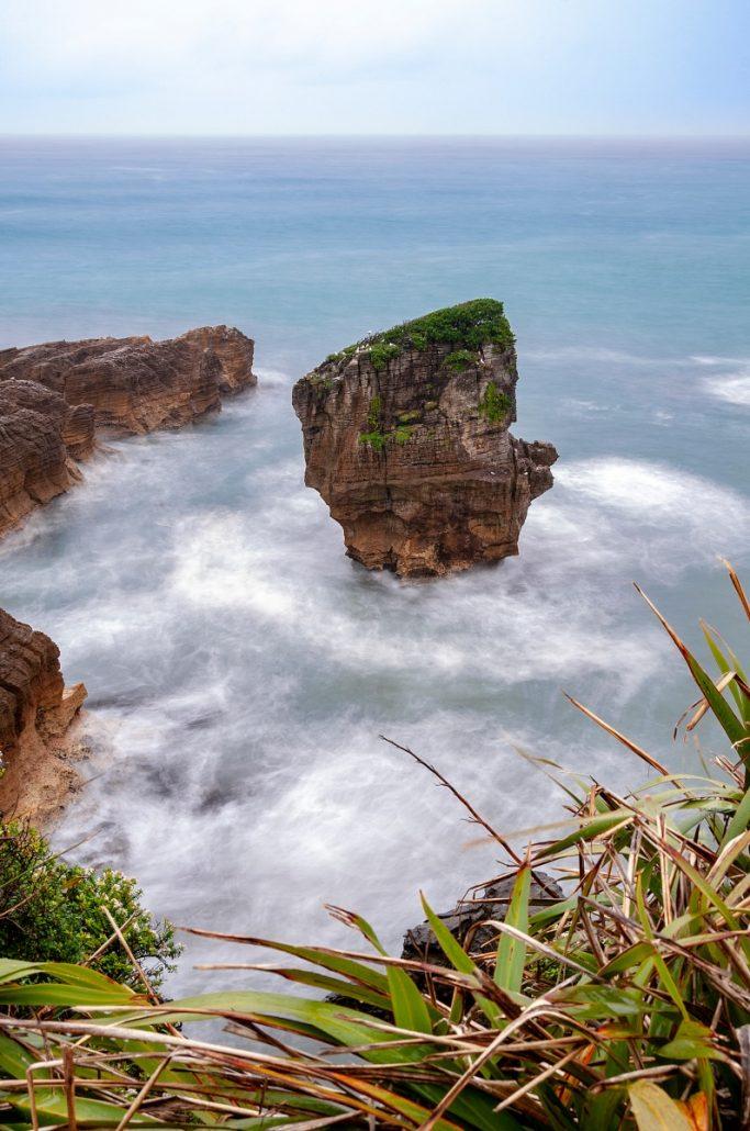 Landscape photograph of a single rock in the sea.